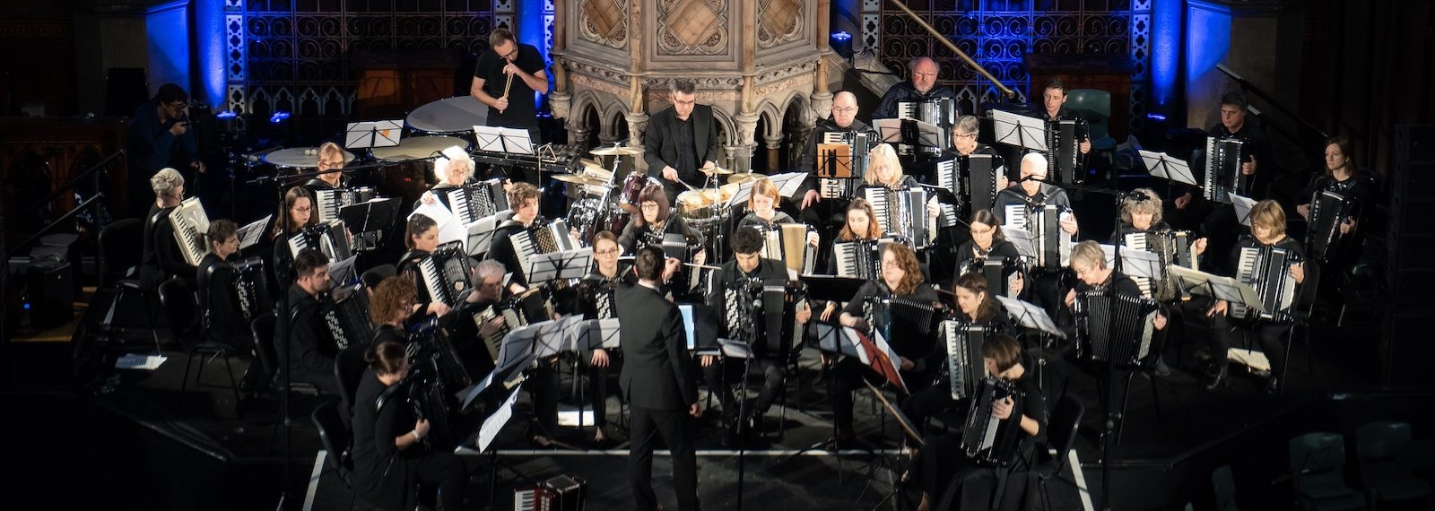 London Accordion Orchestra in concert at Union Chapel in front of blue lights